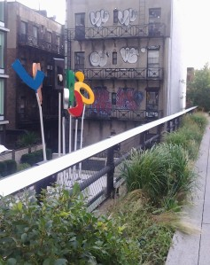 Playful sculptures are found along the Highline, contrasted here with art from the neighborhood's less glamorous past in the background.