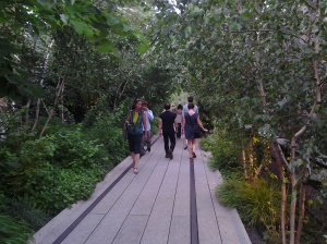 Patrons walk through a grove of trees along NYC's Highline Park.